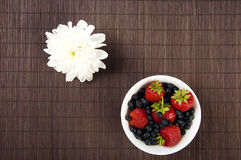 Light Breakfast flower and Berries on a table. Light Breakfast: flower and Berries on a table on a bamboo background Stock Photos