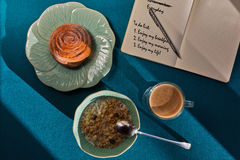Light breakfast in flower-like crockery and a notebook with day. Light luncheon consists of muesli, cinnamon bun and coffee shooted on an aquamarin table near royalty free stock images