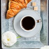 Fresh Croissant, Cup of Coffee and Ranunculus Flowers. Breakfast. Light Breakfast from fresh Croissant and Cup of Coffee on the grey tray, Ranunculus Flowers Stock Images
