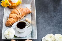 Fresh Croissant, Cup of Coffee and Ranunculus Flowers. Breakfast. Light Breakfast from fresh Croissant and Cup of Coffee on the grey tray, Ranunculus Flowers Royalty Free Stock Image