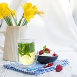 Light breakfast at home, a bouquet of fresh spring flowers in the Kushina. A glass of tea with mint and a bowl of cottage cheese. With berries of red Royalty Free Stock Photos