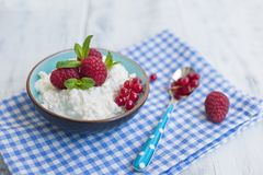 Light breakfast at home, a bowl of cottage cheese with berries of red raspberries and currants. Blue napkin and spoon. Free space. For text or a postcard Royalty Free Stock Images