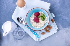 Light breakfast at home, a bowl of cottage cheese with berries of red raspberries and currants. Blue napkin and spoon. Free space. For text or a postcard Stock Photo