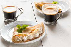 A light breakfast or lunch for two persons. With pancakes (crepes) and whipped cream. On the table is the coffee. Sunny morning, white wooden table Royalty Free Stock Photo