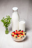 Light breakfast. Milk and corn flakes with berries on wooden background Stock Photo