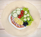 Light breakfast of quail eggs , lettuce, cherry tomatoes, ham , lemon and olives on a wooden background Royalty Free Stock Photos
