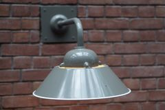 Light on a brick wall. A metal light fixture attached to an old brick wall Stock Photos