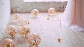 Light bright balloons lie and roll on floor, filled with golden serpentine, glitter in the light of the sun, joyful