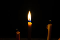 Light candle. Light and bright golden yellow candle amidst darkness Royalty Free Stock Photos