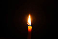 Light candle. Light and bright golden yellow candle amidst darkness Stock Images