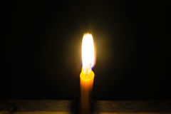 Light candle. Light and bright golden yellow candle amidst darkness Royalty Free Stock Image