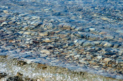 Pebble stones into the water. Light and bright pebble stones into the water Royalty Free Stock Photos