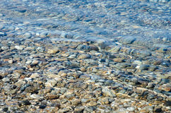 Pebble stones into the water in the lake Baikal. Light and bright pebble stones into the water in the lake Baikal Royalty Free Stock Photography