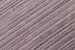 Light brown background of a knitted textile material. Fabric with a striped texture closeup. Royalty Free Stock Image