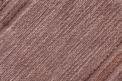 Light brown background of a knitted textile material. Fabric with a striped texture closeup. Stock Photo