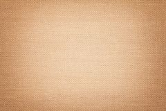 Light brown background from a textile material with wicker pattern, closeup. Structure of the bronze fabric with texture. Cloth beige backdrop with vignette stock image
