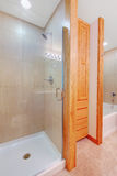 Light brown bathroom interior with wooden storage combination and shower. Stock Photo