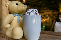 A light brown cute bear with a hot mocha coffee with whipping cream on the wooden table  - apply filter Royalty Free Stock Image