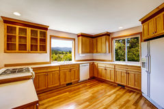 Light brown kitchen cabinets, white appliances and hardwood floor Stock Photography