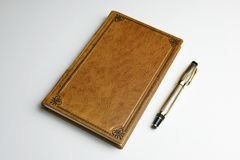 Light brown leather journal with the posted golden fountain pen stock images