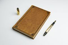 Light brown leather journal with the posted golden fountain pen over the book cover royalty free stock image