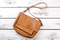 Light brown leather satchel with handle. Top view. White wooden background Stock Photo
