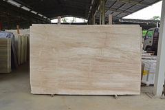 Light brown marble slab displayed within a large warehouse stock photos