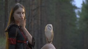 A light brown owl rests on woman knee in the middle of a coniferous forest while she sends an air kiss, slow motion. A light brown owl rests on brunette knee in stock footage