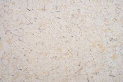 Light brown rice mulberry flower  petal and seed hand made rough paper textured background. Recycled paper.  Natural craft paper. Textured background. Eco royalty free stock photos