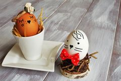 Light brown selfish egg with satin flower in exclusive porcelain coffee pair and white egg with red tie nest from birch twigs on. Brown egocentric egg with royalty free stock images