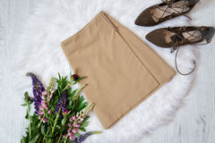 Light brown suede skirt and shoes on white fur, a bouquet of flowers. Fashionable concept Stock Image
