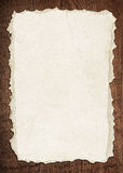 Light brown torn paper is on old wooden board Stock Photo