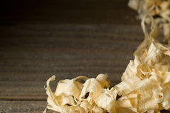 Light brown wood shavings from carpenter`s hand planer or chisel. Work on wooden boards background with copy space Stock Photography