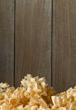 Light brown wood shavings from carpenter`s hand planer or chisel. Work on wooden boards background with copy space Stock Photos