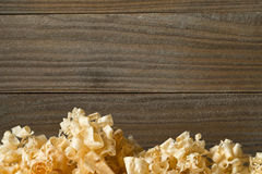 Light brown wood shavings from carpenter`s hand planer or chisel. Work on wooden boards background with copy space Royalty Free Stock Photo