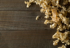Light brown wood shavings from carpenter`s hand planer or chisel. Work on wooden boards background with copy space Royalty Free Stock Images