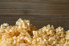 Light brown wood shavings from carpenter`s hand planer or chisel. Work on wooden boards background with copy space Royalty Free Stock Image