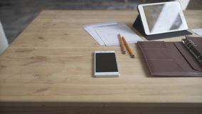 Light brown wooden table work space area desktop with leather case note pad journal tablet cell phone watch coffee cup. Close up shot of elegant light brown stock video footage
