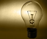 Light bulb. Against deep yellow background Royalty Free Stock Photography
