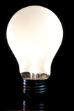 Light Bulb. A lightbulb with screw cap fitting against a black background Stock Images