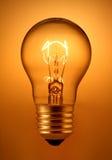 Light bulb. On golden background Stock Photos