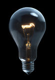 Light bulb. A incandescent light bulb on black background Royalty Free Stock Photography