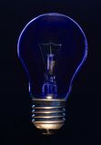 Light bulb. On black background lit with blue light Royalty Free Stock Images