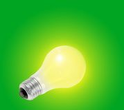 Light bulb. Yellow light bulb with green background royalty free stock photography