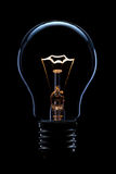 Light bulb. A glowing light bulb on black background Royalty Free Stock Photos