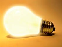 Light bulb. Lit light bulb isolated on orange background stock photography