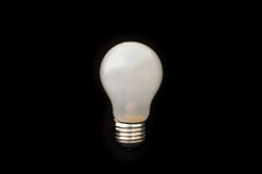 Light bulb. A light bulb on a black background Royalty Free Stock Images