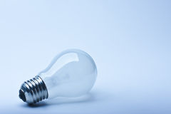 Light bulb. Close-up isolated light bulb in blue lighting Stock Photos