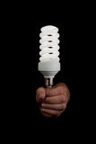Light bulb above hand isolated. Hand holding glowing light bulb on black background. Symbolize idea innovation brilliance Royalty Free Stock Images