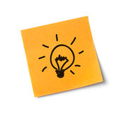 Light bulb on adhesive note Royalty Free Stock Images